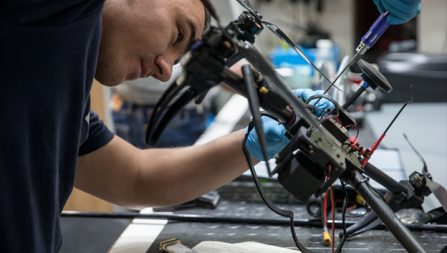 Photograph of a person building a drone in an industrial setting.