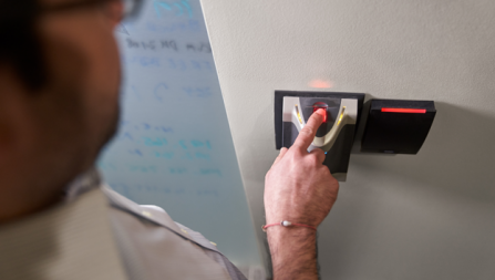 Person scanning a finger in a biometric fingerprint reader to gain access