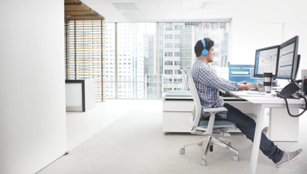 Photo of a person seated at a home office in their condo working on a desktop PC.