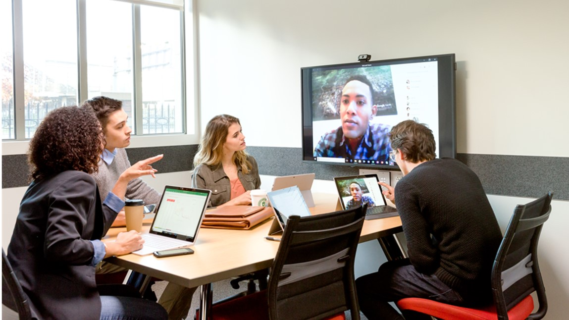people in a meeting room looking at a screen