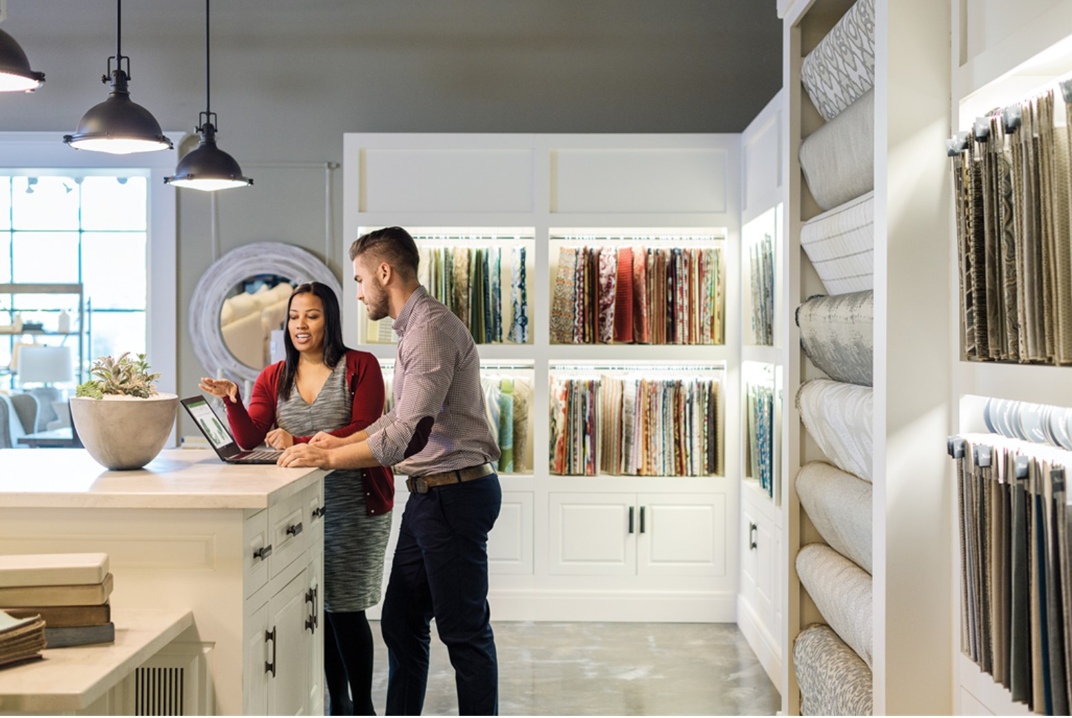 Photograph of a client exploring décor options with the help of a designer in a design studio