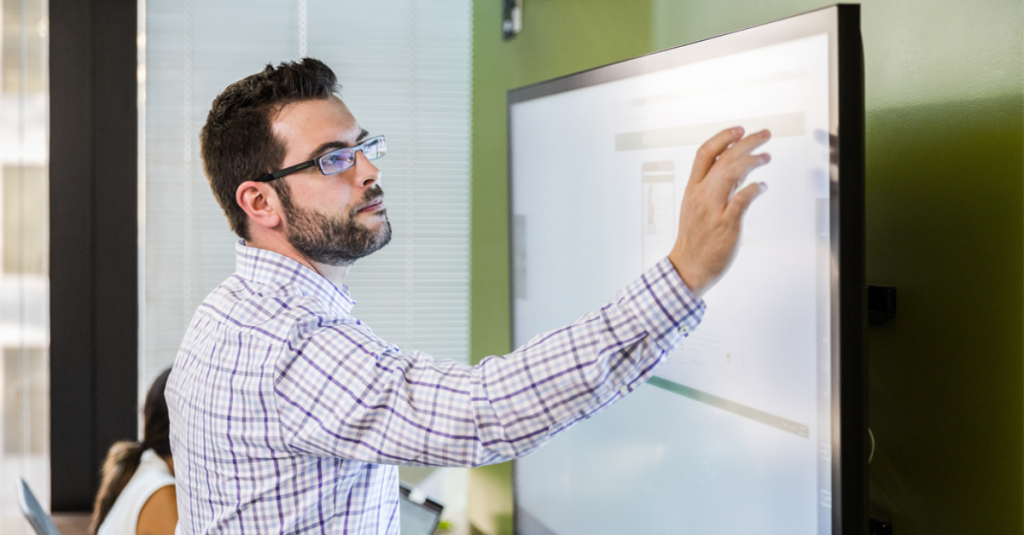 Man pointing to digital whiteboard