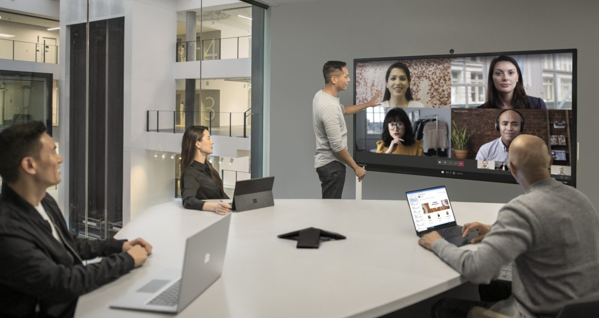 four people conference calling with others on large screen