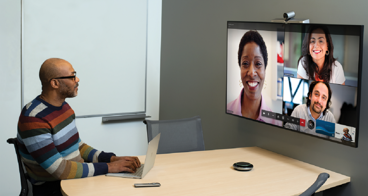 Man videoconferencing from his office with three other people.