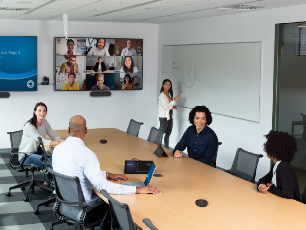 Five people in a conference room holding a video call with nine others.